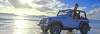 A jeep drives along an Australian beach