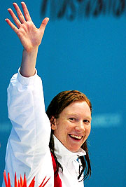 Rebecca Cooke waves to the crowd as they applaud her gold medal 800m swim.