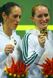 Rachael Grinham (L) of Australia looks at the gold medal of her sister Natalie Grinham.