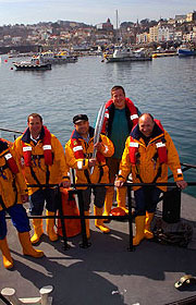 The crew of the life boat Spirit of Guernsey with the Queen's Baton on the small Channel Island.